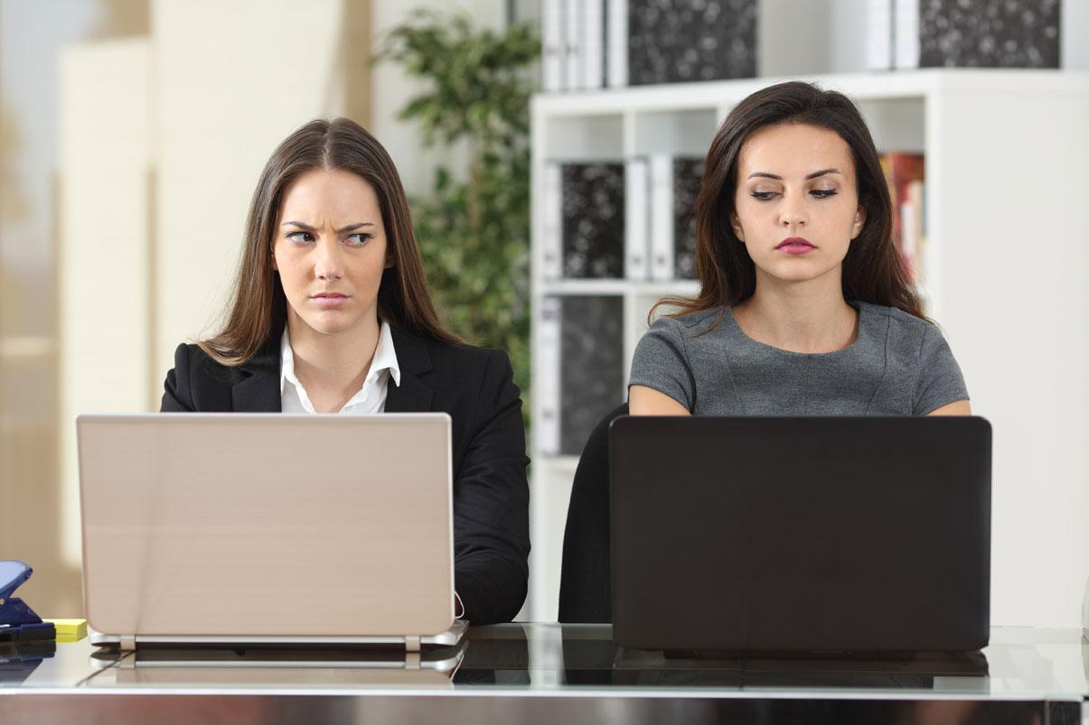 Two women working side-by-side glancing sideways at each other