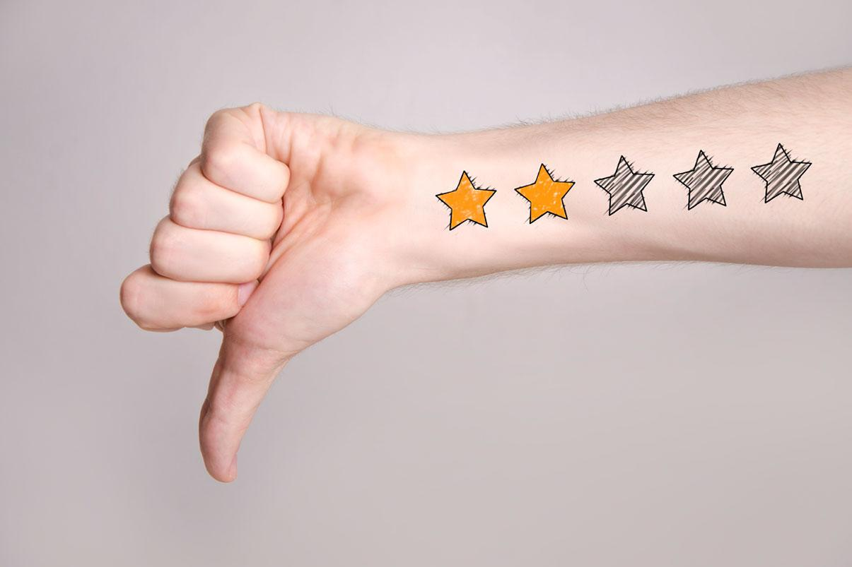 Hand pointing thumbs-down with tattoo of a two-star review on the forearm