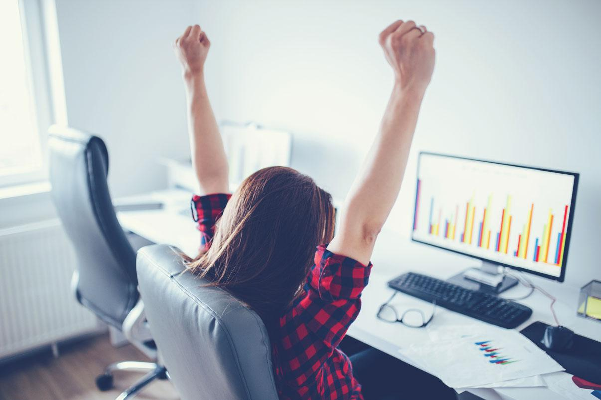 Woman looking at spreadsheet and raising her fists in celebration