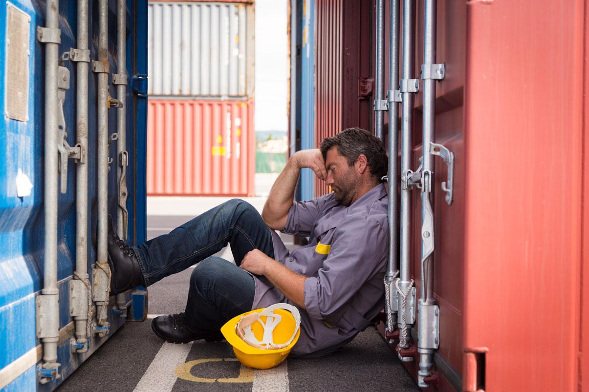 Worker sleeping between two shipping containers